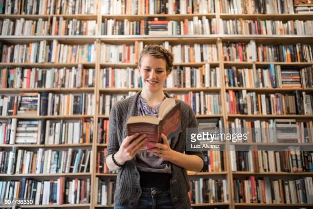 Happy female customer reading book at bookstore