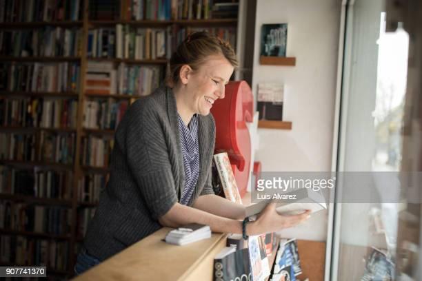 Happy female customer reading book by window