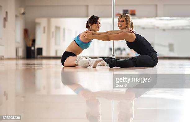 Happy female dancers stretching together in a dance studio.
