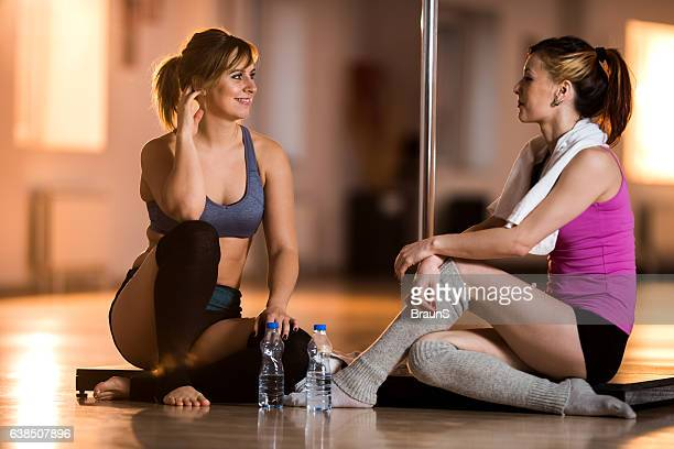 Happy female dancers talking on a break in dance studio.