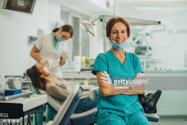 Happy female dentist with crossed arms looking at the camera.