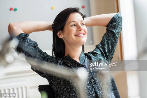 Happy female designer with hands behind her head in creative studio