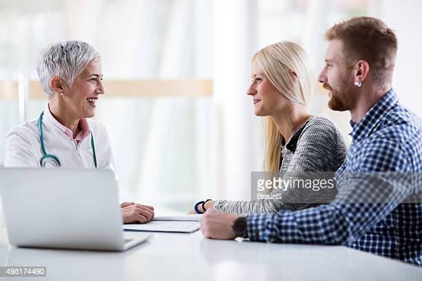 Zufrieden Ärztin einen Termin mit junges Paar.