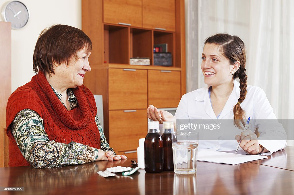 happy female doctor prescribing medication to mature woman : Stock Photo