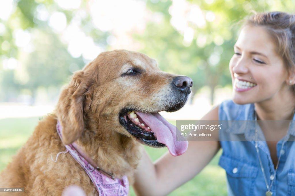 Feliz dueño de perrita juega con el perro en el Parque : Foto de stock