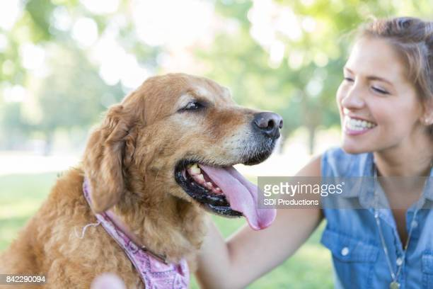 Happy female dog owner plays with dog in the park