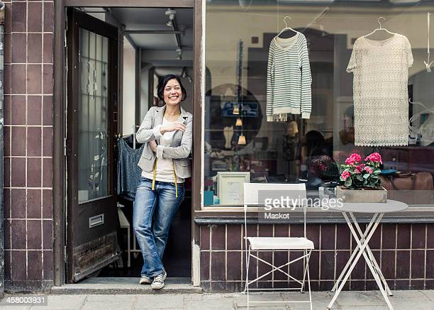 happy female fashion designer looking away while standing at studio doorway - facade stock pictures, royalty-free photos & images