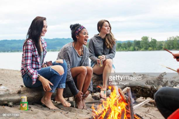 Happy female friend sitting on tree trunk by campfire against river