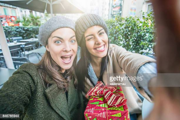 Happy female friends at sidewalk cafe taking a selfie while doing Christmas shopping