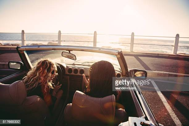 Happy female friends cheering in a convertible at sunset