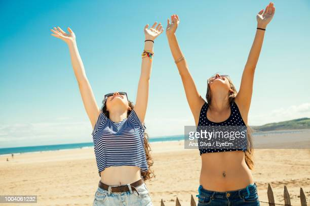 happy female friends enjoying at beach during sunny day - arms raised stock pictures, royalty-free photos & images