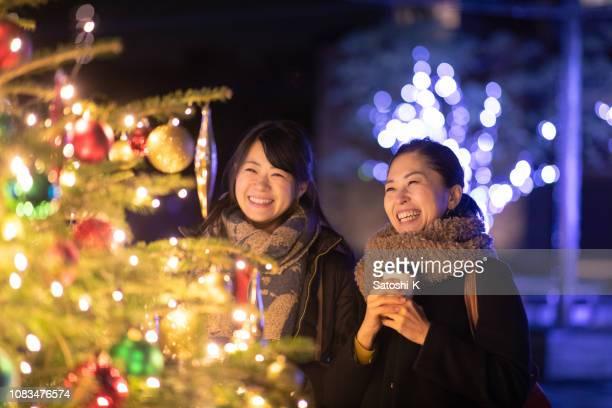 クリスマスのイルミネーションを楽しんで幸せな女性の友人 - イルミネーション ストックフォトと画像