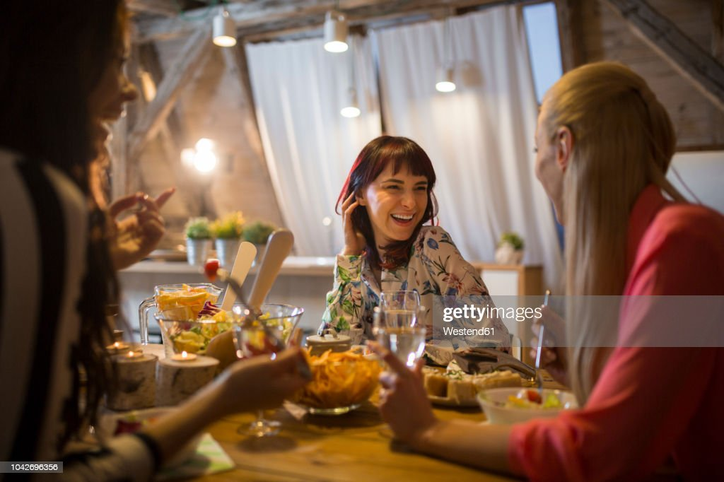 Happy female friends having dinner at home together : Stock Photo