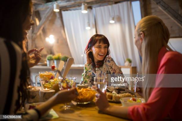 happy female friends having dinner at home together - warmes abendessen stock-fotos und bilder