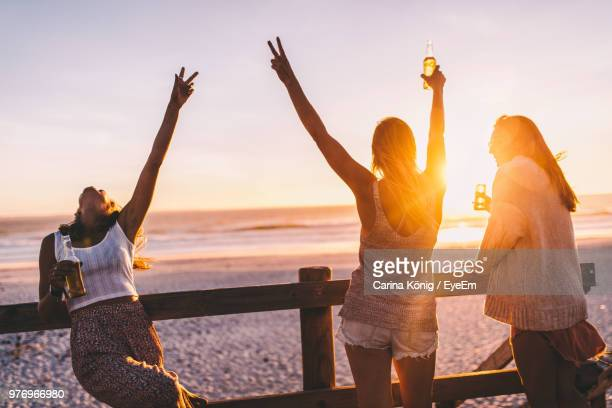 happy female friends having drink at beach during sunset - beer alcohol stock pictures, royalty-free photos & images