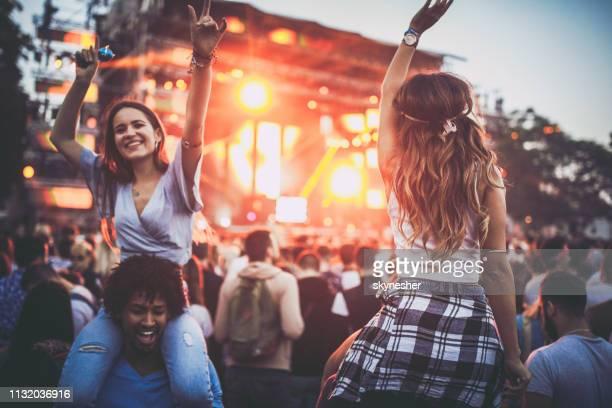 amigos fêmeas felizes que têm o divertimento em um concerto da música. - músico pop - fotografias e filmes do acervo