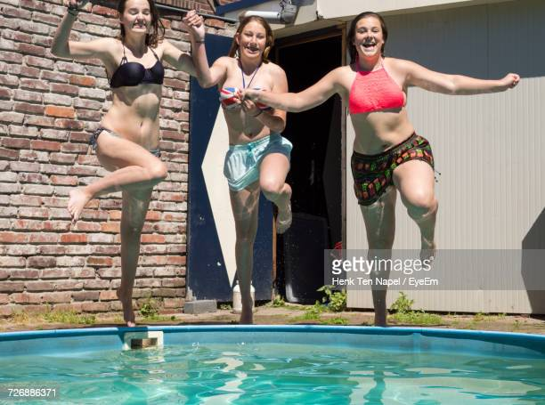 Happy Female Friends Jumping In Swimming Pool