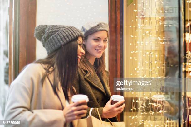 Happy female friends looking at store window for the Christmas shopping