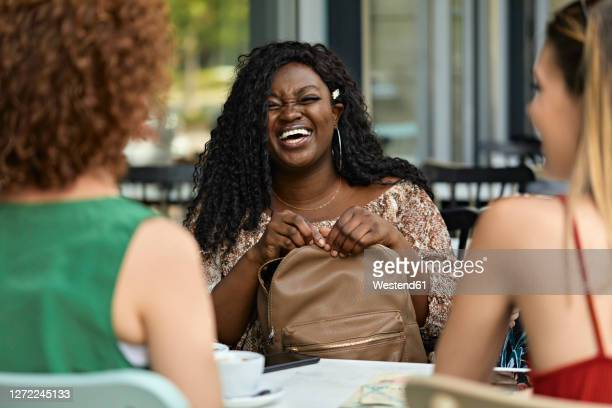 happy female friends meeting in a cafe - black purse stock pictures, royalty-free photos & images
