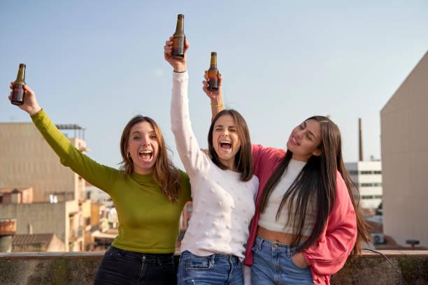 Happy female friends raising beer bottles enjoying on rooftop