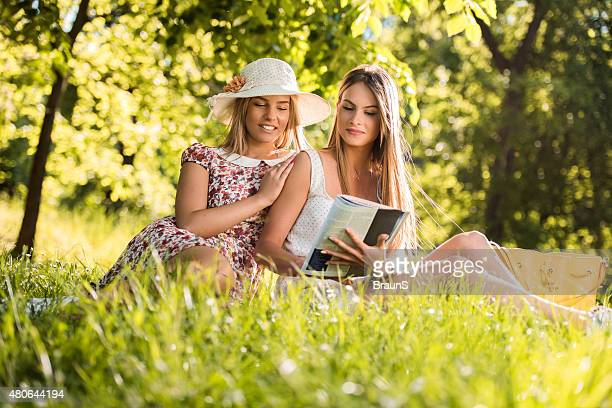 happy female friends reading a magazine at the park. - nature magazine stock pictures, royalty-free photos & images
