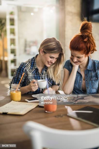 happy female friends reading a magazine in a cafe. - magazine stock pictures, royalty-free photos & images