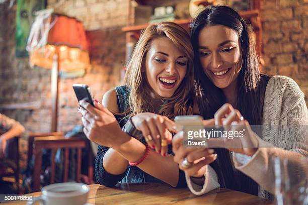 happy female friends reading a text message on cell phone. - two objects stock photos and pictures