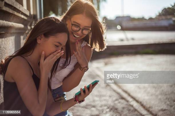 happy female friends reading a text message outdoors - a prates a foto e immagini stock