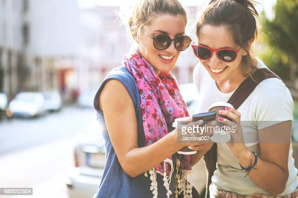 Happy female friends reading a text message outdoors