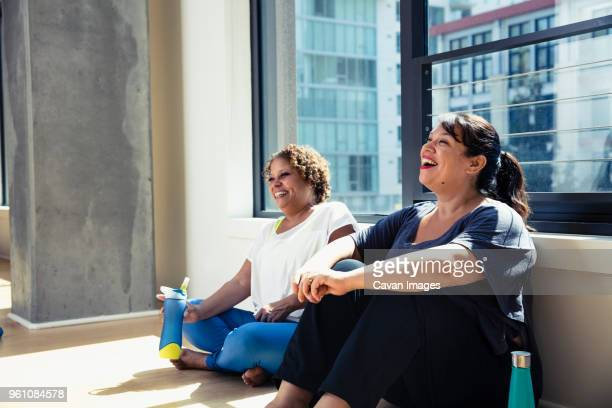 happy female friends sitting against window in yoga studio - overweight stock pictures, royalty-free photos & images