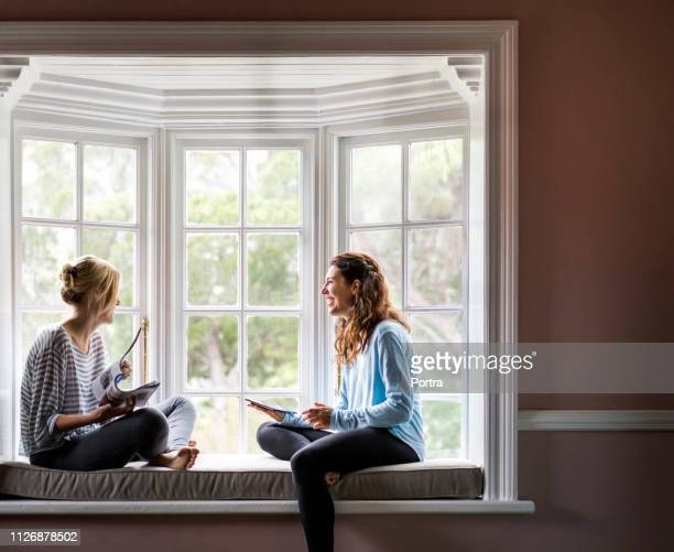 happy female friends sitting on alcove window seat - ammunition magazine stock photos and pictures