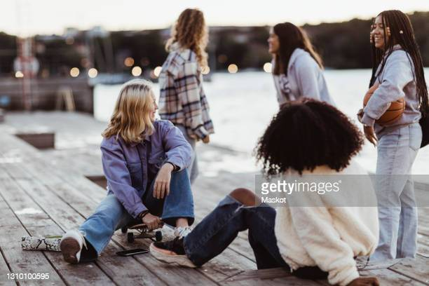 happy female friends spending leisure time on pier during sunset - sweden stock pictures, royalty-free photos & images