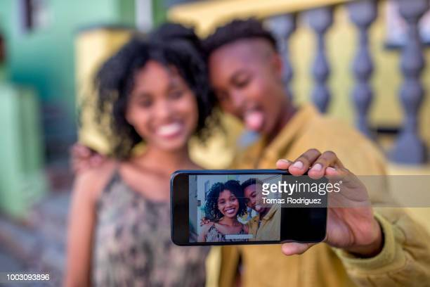 Happy female friends taking a selfie outdoors