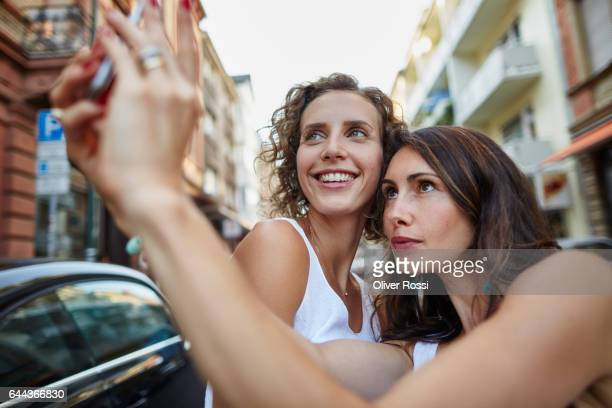 happy female friends taking a selfie outdoors - only mid adult women stock pictures, royalty-free photos & images