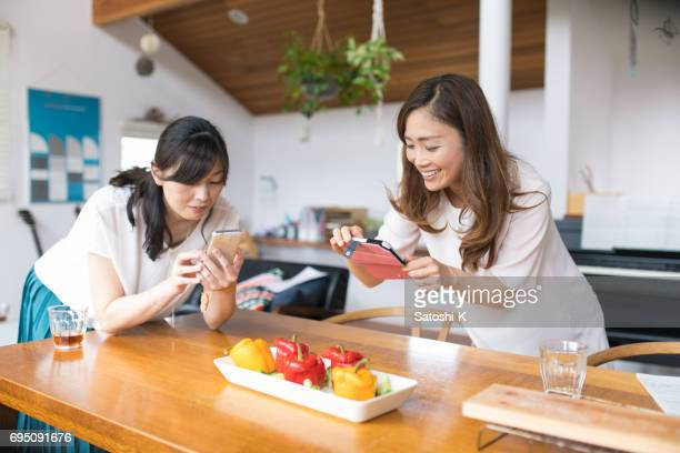 happy female friends taking pictures of paprika dish before lunch - capturing an image stock pictures, royalty-free photos & images