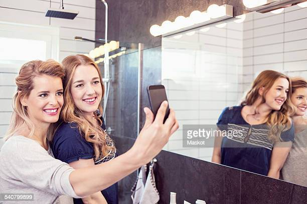 Happy female friends taking self-portrait with cell phone in bathroom
