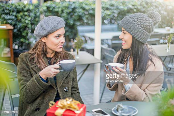 Happy female friends talking at sidewalk cafe
