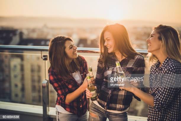 Gelukkig vriendinnen praten tijdens het drinken van bier op een terras bij zonsondergang.