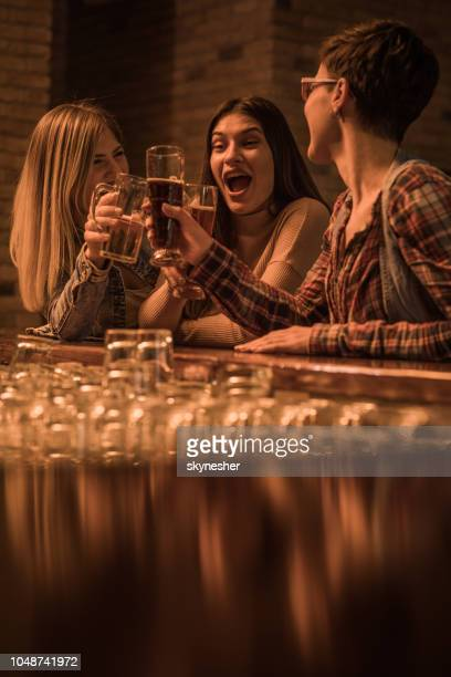 happy female friends toasting with beer at bar counter. - brindisi bicchieri foto e immagini stock
