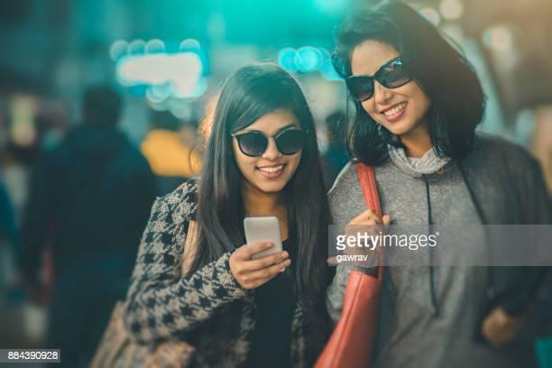 glücklich freundinnen im markt zusammen. - mensch im hintergrund stock-fotos und bilder