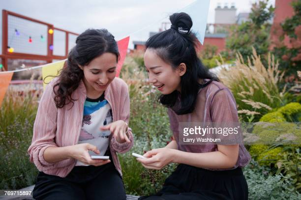Happy female friends using smart phones while sitting on patio