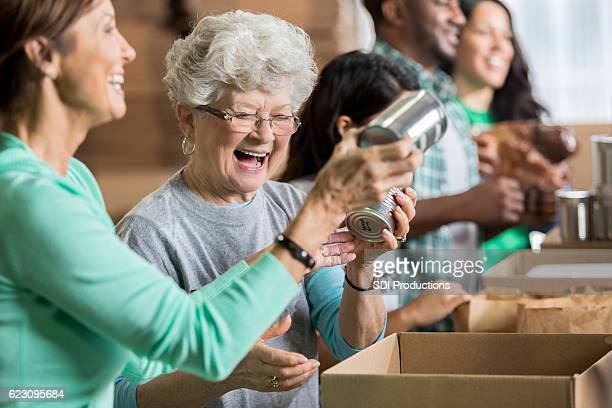 Happy female friends volunteer at charity food bank
