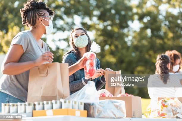 les amies heureuses font du bénévolat à la banque alimentaire - gratuit photos et images de collection