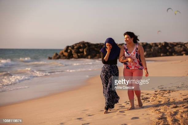Happy female friends walking and laughing at beach
