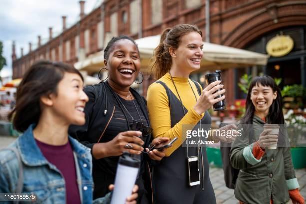 happy female friends with drinks walking in city - travel stock-fotos und bilder
