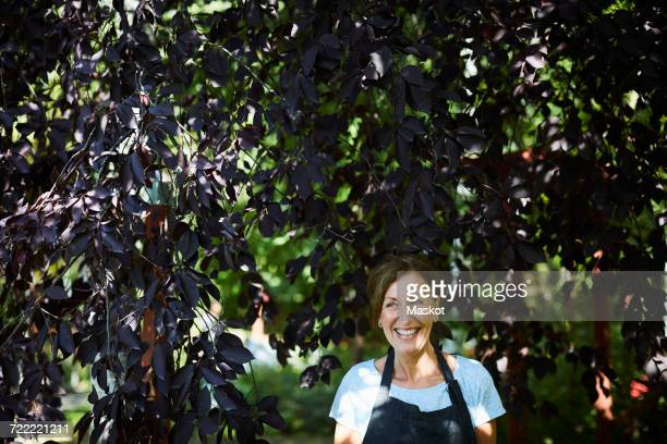 Happy female gardener surrounded by branches in yard
