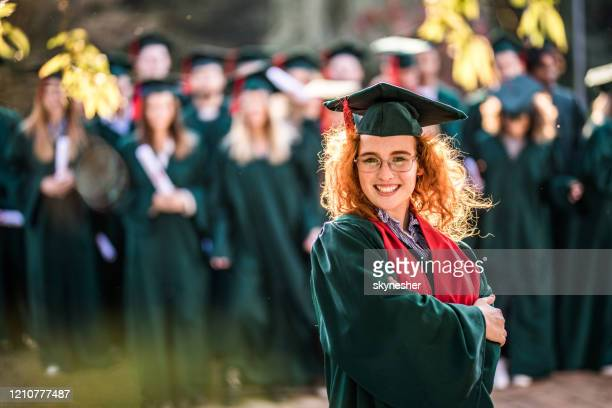 happy female graduate with crossed arms looking at camera. - alumni stock pictures, royalty-free photos & images