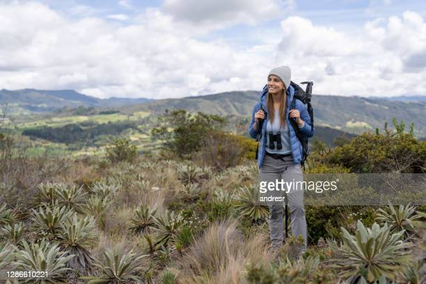 happy female hiker carrying her backpack in the mountain while enjoying nature - binoculars stock pictures, royalty-free photos & images