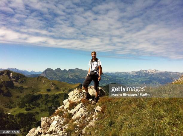 happy female hiker standing on field at mountains against sky - liechtenstein stock pictures, royalty-free photos & images