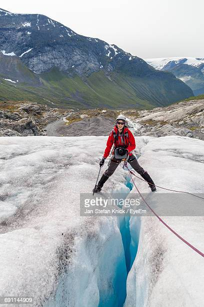 happy female hiker standing on glacier crack against mountain - crevasse stock photos and pictures
